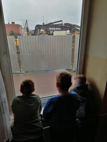 Chłopcy z okna klasy przyglądaja się pracy koparki